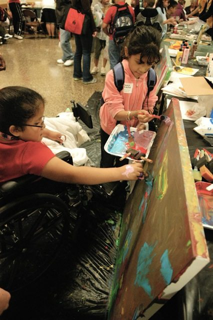 Two special needs girls painting a large canvas