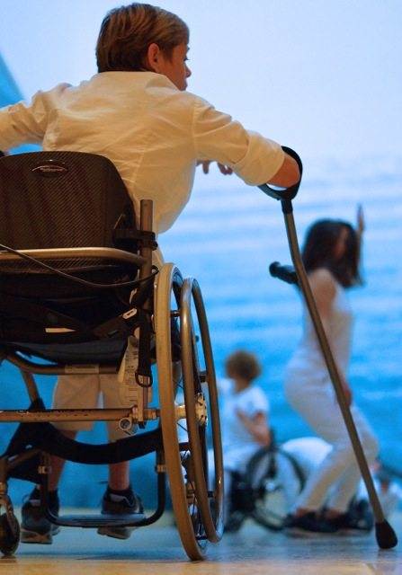 Woman in wheelchair with a crutch