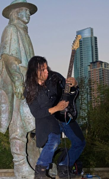 Long haired man playing electric guitar in front of green copper statue