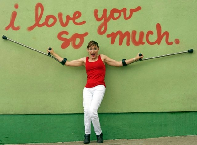 """Woman in red shirt holding up arm brace crutches in front of Austin's """"i love you so much"""" spray painted wall"""