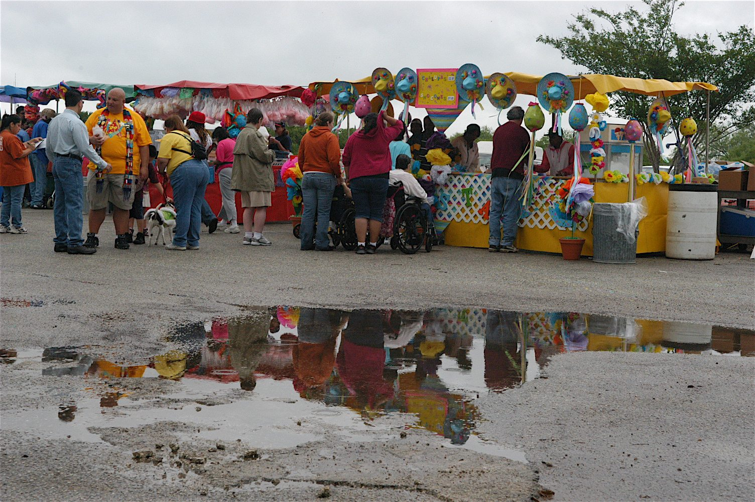 Group of people in line at a vendor at a small festival with a puddle in the foreground
